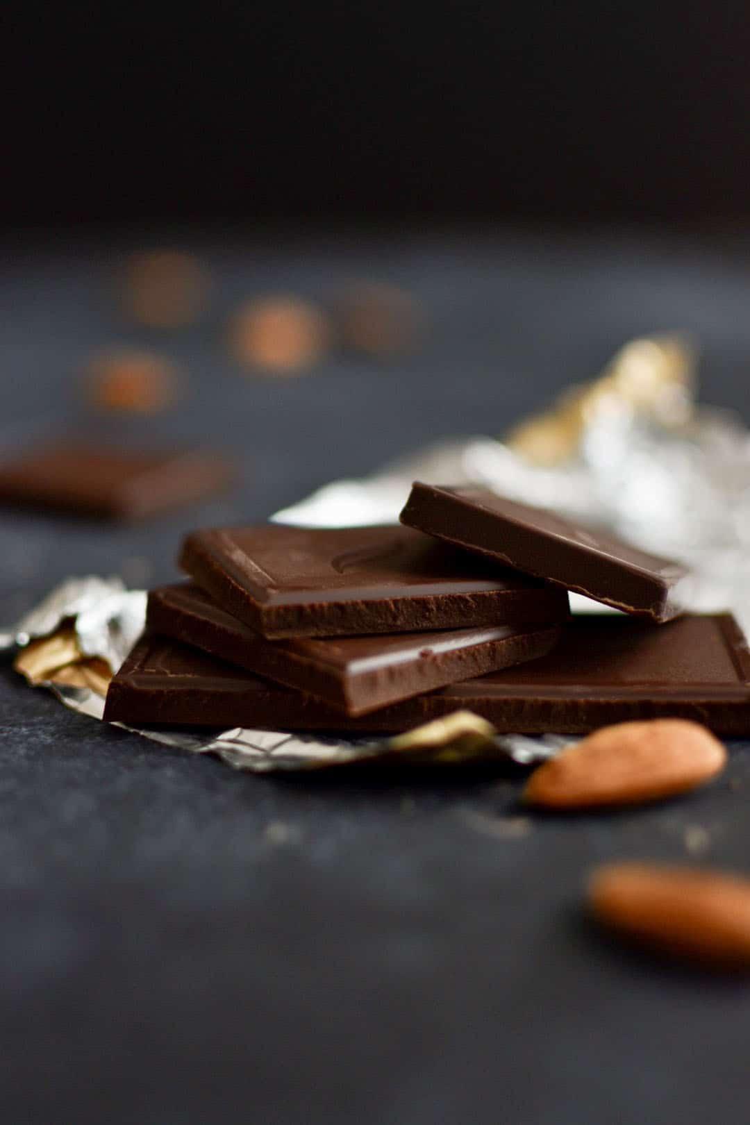 Carrés de chocolat noir sur fond noir avec amandes