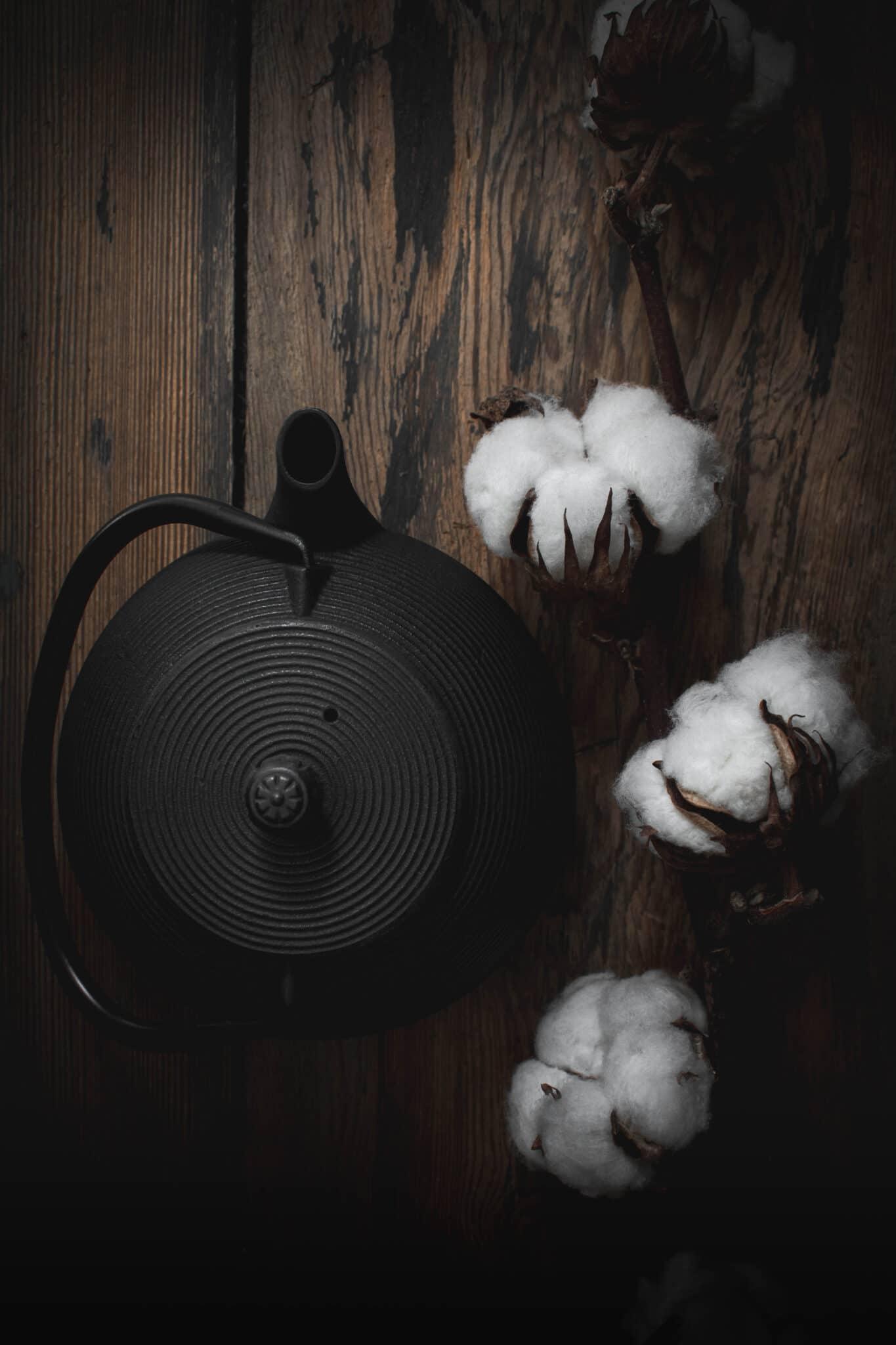 théière en fonte et coton sur fond bois vieilli