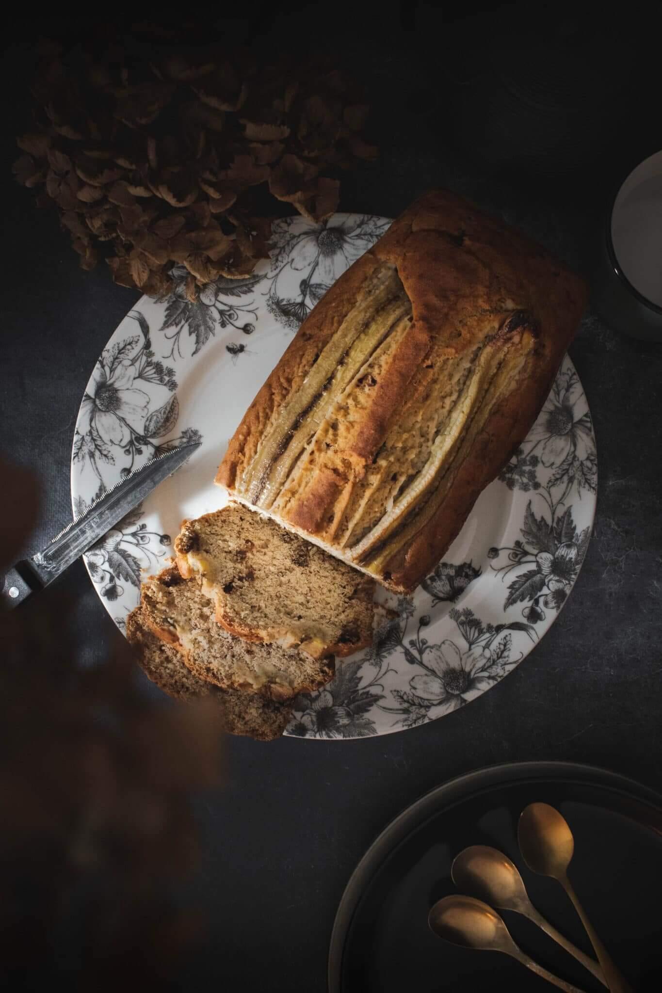 Banana bread vu de dessus sur assiette fleurie avec hortensias séchés