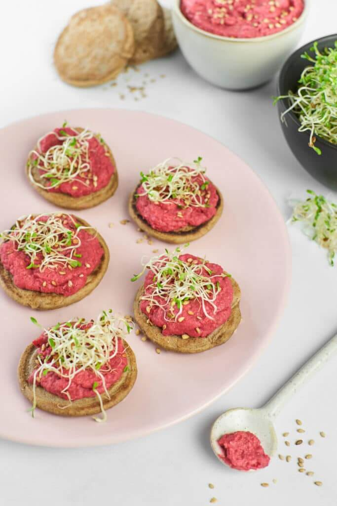 Blinis et houmous de betterave dans assiette rose