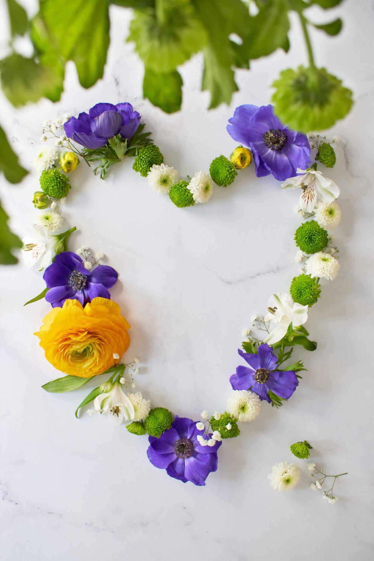 Couronne de fleurs formant un coeur sur fond marbre