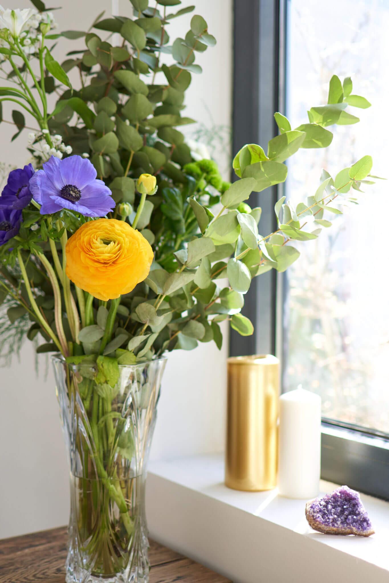 Fleurs, bougies et pierres naturelles devant fenêtre